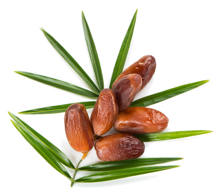 Top view of dried dates on stalk with green leaves isolated on white background