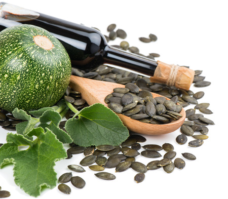 Pumpkin seed oil in bottle with seeds and pumpkin with green leaves  isolated on white background