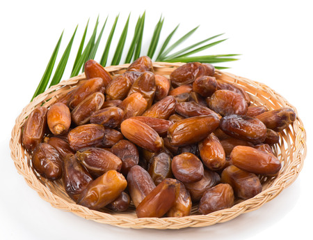 dried dates on wicker plate with green leaf of palm tree isolated on white background. Selective focus located in the middle of the plate