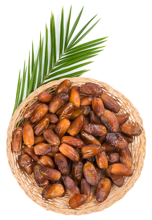 green dates: shot from above of dried dates on wicker plate with green leaf of palm tree isolated on white background Stock Photo