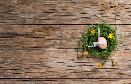 speckled wood: Top view of egg in a nest from green grass with yellow flowers over old wooden background with copy-space Stock Photo