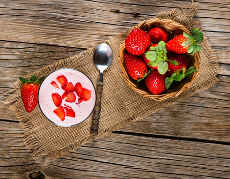 Fresh Organic Greek Yogurt with strawberries on a wooden background, top view Stockfoto