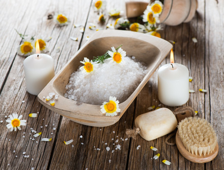 Natural Spa Treatment with  chamomile flowers on wooden  background photo
