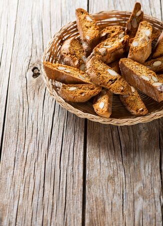Traditional Italian biscotti with almond in a wicker tray on wooden table, copy space for your text photo
