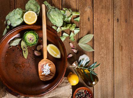 aceite de cocina: Vista superior de alcachofas frescas listas para ser preparado para la cena con pimienta, aceite de oliva, limón, especias para un horneado. Copiar el espacio para el texto.