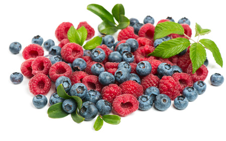 pile of leaves: Raspberries and blueberries pile with leaves isolated on white