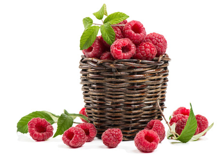 raw food: Fresh organic raspberry with leaves in basket isolated on a white