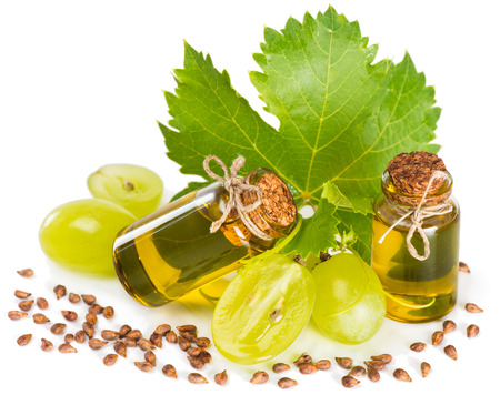 Grape seed oil in a glass bottles isolated on white background Foto de archivo