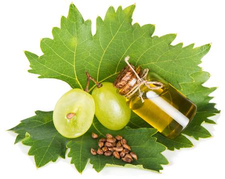 Petite bouteille avec de l'huile de pépins de raisin, les graines et les raisins sur une vigne de feuille isolé sur fond blanc Banque d'images - 38611713