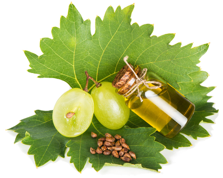 Small bottle with grape seed oil, seeds and grapes on a leaf vine isolated on white background