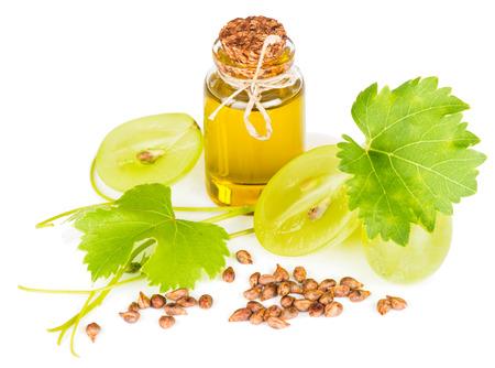 aceites: Aceite de semilla de uva en una botella de vidrio, semillas y frutas con hojas aisladas sobre fondo blanco