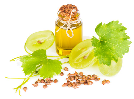 Grape seed oil in a glass bottle, seeds and fruit with leaves isolated on white background