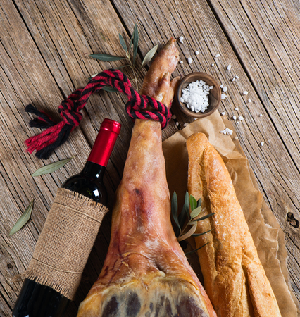 Full leg of smoked ham, bottle of red wine, bread and salt top view on a wooden old  background photo