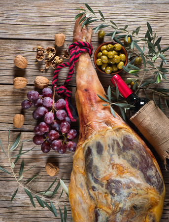aperitive: View from above of iberico ham leg, cheese, walnuts and bottle of red wine