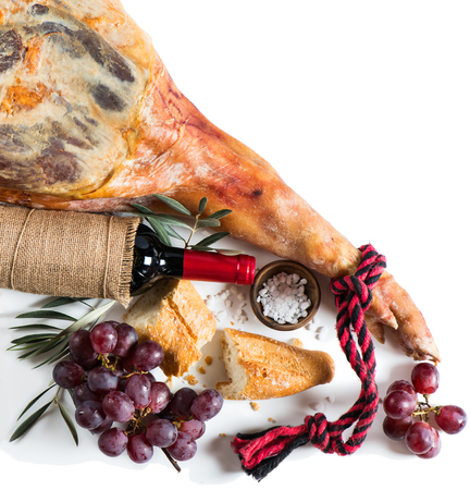 bread and wine: Leg of spanish serrano ham,  bread, wine and grapes isolated on a white background