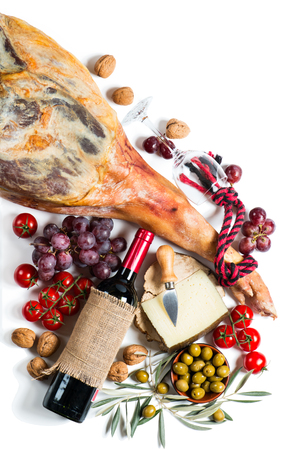 aperitive: Full leg of spanish serrano ham, red wine and  tapas.  Isolated on a white background, top view. Stock Photo