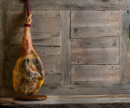 Jamon serrano on a wooden old background with space for text photo