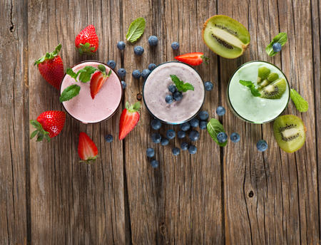 Top view of assorted smoothies of berry on a rustic wooden background