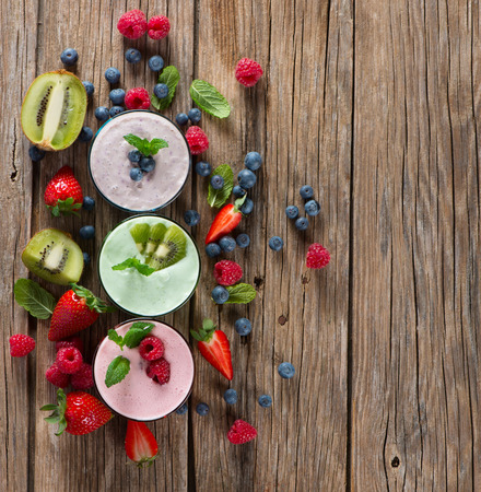 glass table: Different smoothies and fresh berry on a rustic wooden background, top view