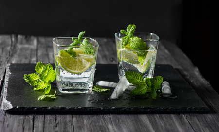 Two glasses of mojito cocktail on a black slate board with copy space for text 스톡 콘텐츠