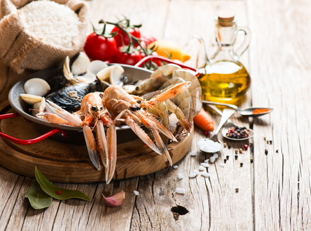 kitchen spanish: Uncooked products of seafood paella on a wooden table Stock Photo