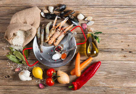 above view: Raw products of seafood paella on a wooden table, view from above. Copy space for text. Stock Photo