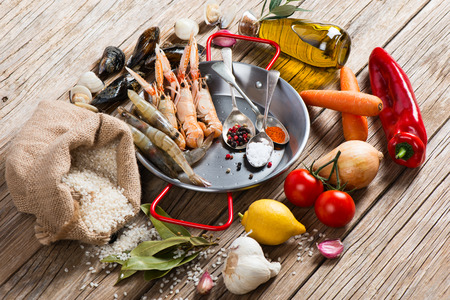 kitchen spanish: Uncooked ingredients of spanish seafood paella on a rustic wooden background