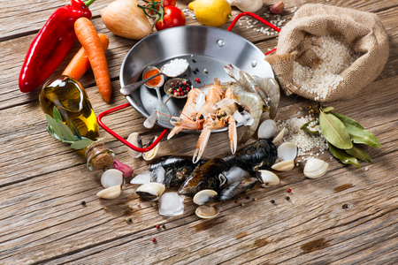 kitchen spanish: Fresh products ready to be prepared for  of spanish seafood paella on a old wooden background
