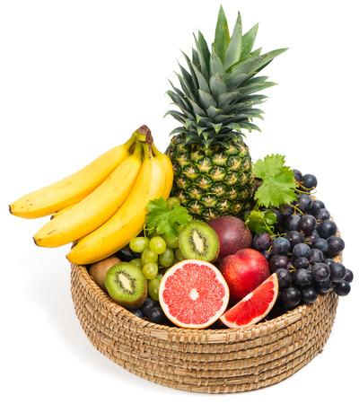 Frutas tropicales en una canasta aislados sobre fondo blanco.