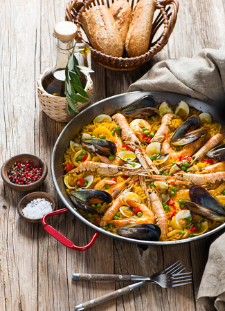 Typical spanish seafood paella in traditional pan on a rustic wooden background