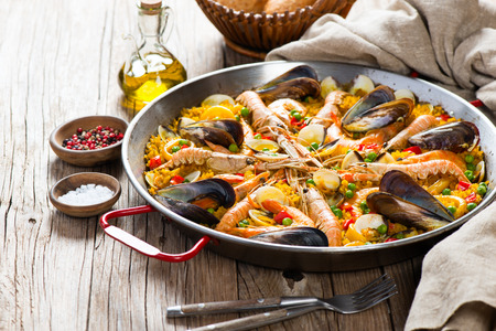 Traditional seafood paella in the fry pan on a wooden old table Standard-Bild