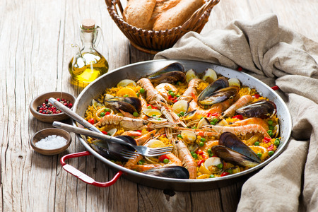 Seafood paella in the fry pan on a wooden rustic table