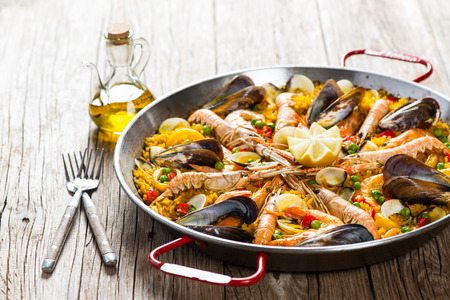 Vegetable paella with seafood on a wooden background