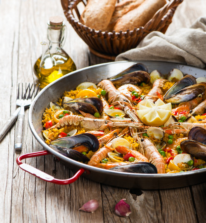 pans: Traditional pan with spanish seafood paella on a rustic wooden table. Selective focus. Stock Photo