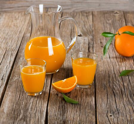 carafe: Glassfuls and pitcher of orange juice on a old wooden table