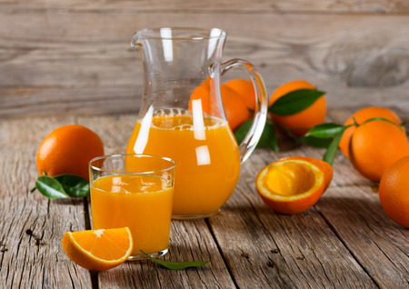 carafe: Orange juice, slice and wholes oranges on a rustic wooden background. Selective focus. Stock Photo