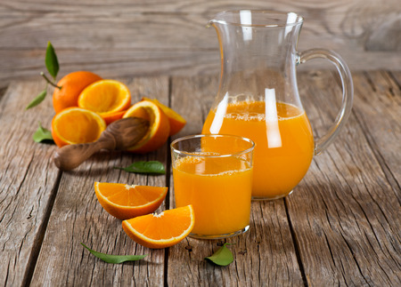orange fruit: Glass and jug of squeezed orange juice on wooden background