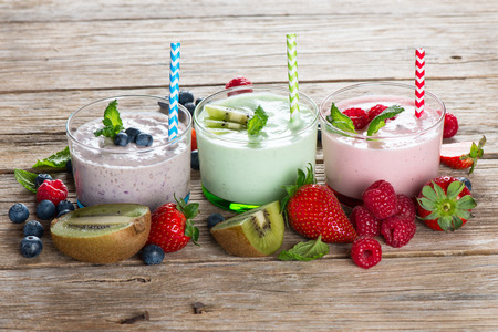 Fruit and berry healthy smoothies on a rustic wooden background photo