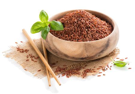 arroz chino: Arroz rojo crudo en un tazón de madera aislada sobre fondo blanco Foto de archivo