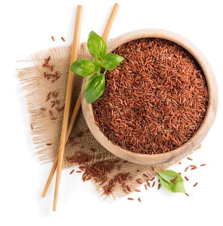 흰 배경에 고립 된 나무 보 울에서 생 쌀된 빨간 쌀의 상위 뷰