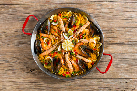 Top view of typical spanish seafood paella in traditional pan on a old wooden background
