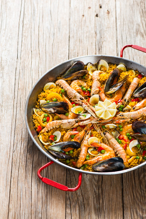 Paella with seafood and vegetables in a pan on a old wooden background