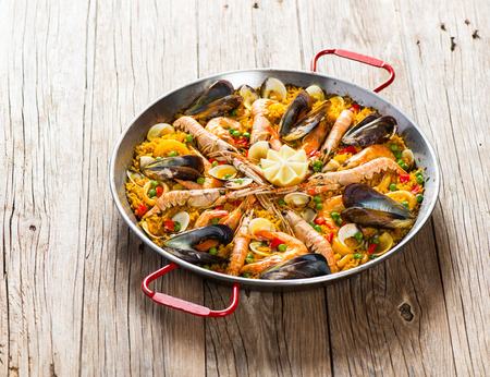 Spanish paella with shrimp and mussel in traditional pan on a old wooden table