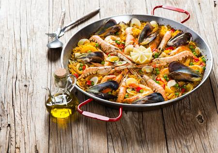 スペイン料理と伝統的な素朴な木製のテーブルの上でシーフードのパエリア