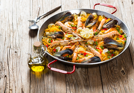 Spanish dish paella with seafood  in traditional pan on a rustic wooden table