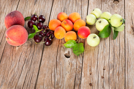 Different fruits (apples, cherries, apricots, and peaches) with leaves on a old wooden planks photo