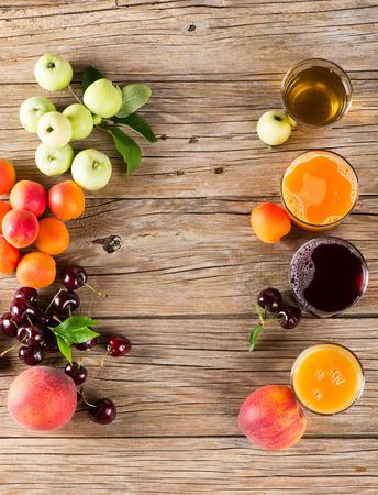 trompo de madera: Gafas de sabrosos jugos y frutas frescas de verano en una mesa de madera vieja, vista aérea