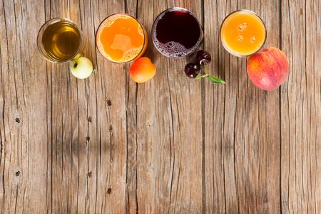 vaso de jugo: Cuatro variedades de jugo en vasos y frutas frescas en un fondo de madera rústica, con espacio para el texto, vista desde arriba.