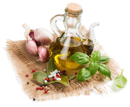 aceite de cocina: Aceite de oliva, ajo, pimienta, sal, laurel y ramita de albahaca en una servilleta de arpillera aislado en un fondo blanco