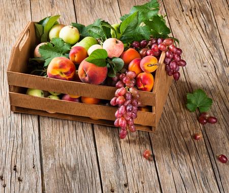 Verschillende soorten fruit opgeslagen in houten kist op een rustieke houten achtergrond